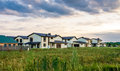 Row of new houses near green field and cloudy sky Royalty Free Stock Photography