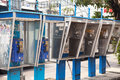 Row of old dirty payphones on a street in Thailand. Group of blu Royalty Free Stock Photo