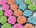 The row of orange, blue, green and pink of cup cake with colorful rounded sugar beads on the cream.