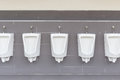 Row of outdoor urinals on grey wall in men public toilet Royalty Free Stock Photo