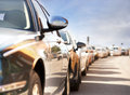 Row of parked cars with reflection traffic and buildings Royalty Free Stock Photo