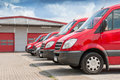 Row of red delivery and service cars in front a factory warehouse distribution plant Royalty Free Stock Photo