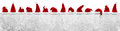 Row of red white santa claus christmas xmas hat on empty concret Royalty Free Stock Photo