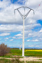Row of rural electrical power lines crossing an empty open green field Stock Photo