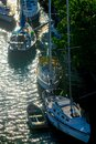 A row of sailboats and dinghies anchored in a sunlit stream Royalty Free Stock Photo