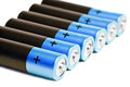 A row from seven blue finger type batteries of the aa size on a white background accumulators close up Stock Photos