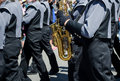 A row of shiny brass instruments are played by a marching band in a parade Stock Images