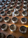 Row of silvery alms bowls with little coins inside in buddhist temple