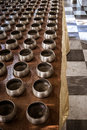 Row of silvery alms bowls with little coins inside in buddhist temple Royalty Free Stock Photo