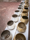 Row of silvery and golden alms bowls in buddhist temple