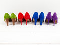 Row of suede stiletto shoes colourful on a white floor infront a white wall Royalty Free Stock Image