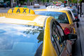 Row of taxi cabs empty waiting for passengers in a city Royalty Free Stock Image