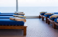 Row of teak cushion bed chairs with towels reclining couches or benches cushions and towel by window looking out to sea horizon in Royalty Free Stock Images