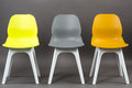Row of three color plastic chairs isolated on gray background. Furniture series. Royalty Free Stock Photo