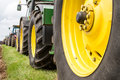 A row of tractor wheels parked up in line on grass verge Stock Photo