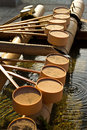 Row of traditional purification dipper at the entrance to a japanese temple Royalty Free Stock Photo