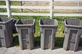 Row of trash bins are empty and are place in front a fence Royalty Free Stock Image
