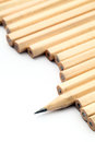 Row of unused pencil with one sharpened over white background Stock Images