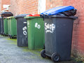 Row of Wheelie Bins in alley with rubbish overflowing