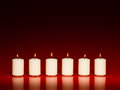 Row of white burning candles Royalty Free Stock Photo
