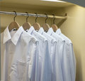 Row of white shirts hanging in wardrobe Royalty Free Stock Photo