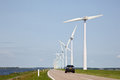 Row of wind turbines and car on dike in the netherlands Stock Photo