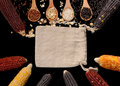 row of wood spoons with various rice with straw rice bag place and colorful corn Royalty Free Stock Photo