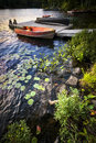 Rowboat at lake shore at dusk tied to dock on beautiful rocky with aquatic plants ontario canada Stock Photography