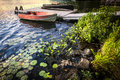 Rowboat at lake shore at dusk tied to dock on beautiful rocky with aquatic plants ontario canada Royalty Free Stock Image