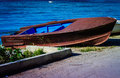 Rowboat left on the shore a in a bright and warm day a in a seaside avenue near town Royalty Free Stock Photo