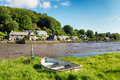 Rowing boat at lerryn an old moored to a grassy bank on the river in cornwall Royalty Free Stock Images