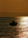 Rowing in sunset alone young man a small wooden boat to paddle a beautiful golden vertical color photo Royalty Free Stock Photography