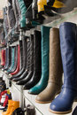 Rows of beautiful female boots on store shelves. Stock Images