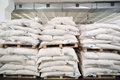 Rows of big white sacks at large warehouse in modern factory Royalty Free Stock Image