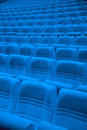 Rows of blue arm chairs in empty hall auditorium Stock Photography
