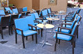 Rows of blue chairs and metallic tables in caffe