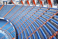 Rows of blue grandstand for fans at football stadium round big Stock Image