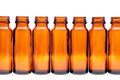 Rows of brown glass bottles isolated on white background Stock Images