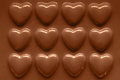 Rows of chocolate hearts photo in a row smothered in smooth melted milk Royalty Free Stock Photography