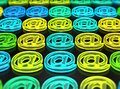Rows of glassy e-mail symbols, green, yellow and blue neon light Royalty Free Stock Photo