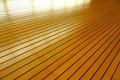 Rows of golden tightly fitted wooden slats background form disappear into infinity with reflections light Royalty Free Stock Photo