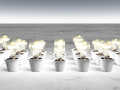 Rows of light bulbs with cold light and different sizes are growing in white pots that lie on a white and gray abstract Royalty Free Stock Image