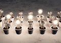 Rows of light bulbs with different sizes in white pots lie on a white and gray abstract ground some are lit randomly Stock Images