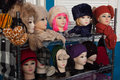 Rows of manikins modelling a range of hats and scarfs manikin heads ear muffs on market stall Royalty Free Stock Photography