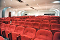 Rows of red seats in an auditorium empty for spectators cinema or entertainment venue viewed close up Stock Image
