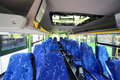 Rows of soft seats inside saloon of empty city bus blue with skylight Stock Photos