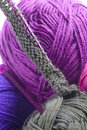 Rows of stitches on a knitting needle grey pearl cast plastic amongst balls colorful purple and grey wool showing the texture Royalty Free Stock Images