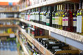 Rows of wine bottles on the shelves in store Royalty Free Stock Images