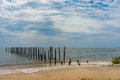 2 rows of wooden posts go out in to a calm paradise sea off of a Royalty Free Stock Photo