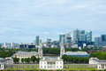 Royal chapel, Painted hall and classic colonnade in Greenwich park, London, and skyscrapers of Canary Wharf in the distance. Royalty Free Stock Photo